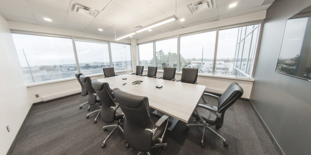 Board room with large windows, table, and chairs