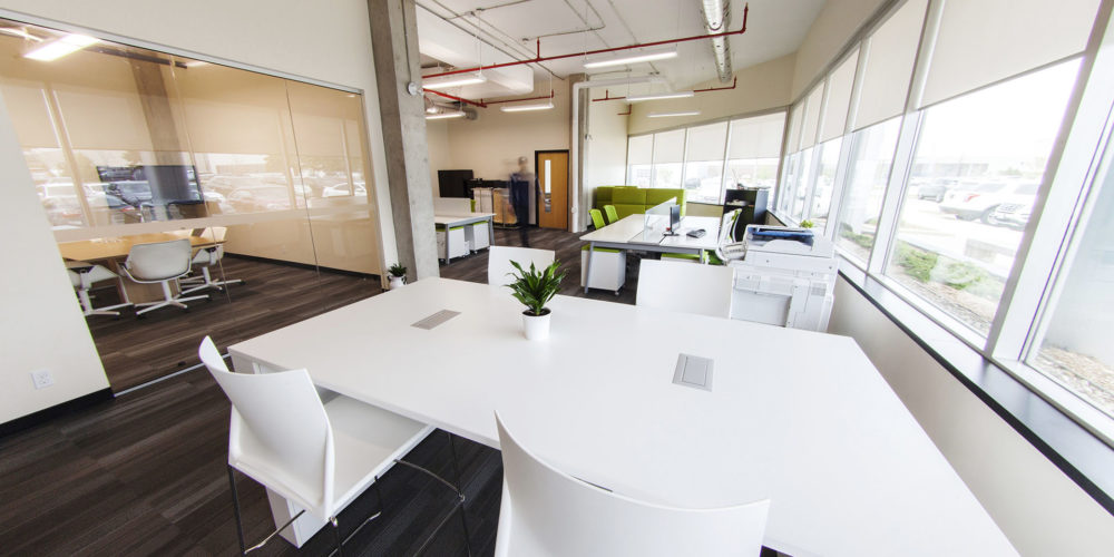 Large open office meeting space with table and chairs